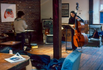 Artist Judy Rifka (left) prepares for her exhibition while French contrabassist Joelle Leandre (right) practices at Hallwalls, 1977.